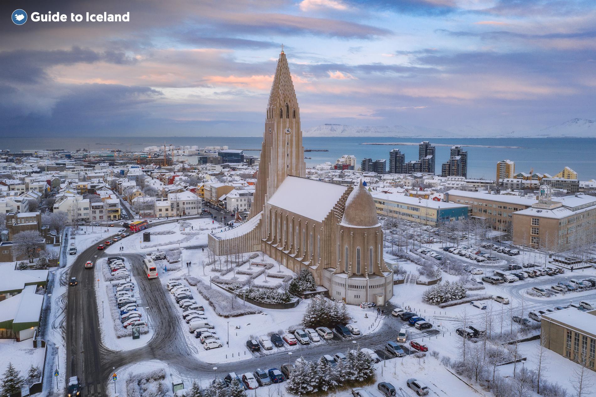 Lo skyline di Reykjavík circondato da una sfumatura dorata attraverso lo stagno ghiacciato di Tjörnin in inverno.