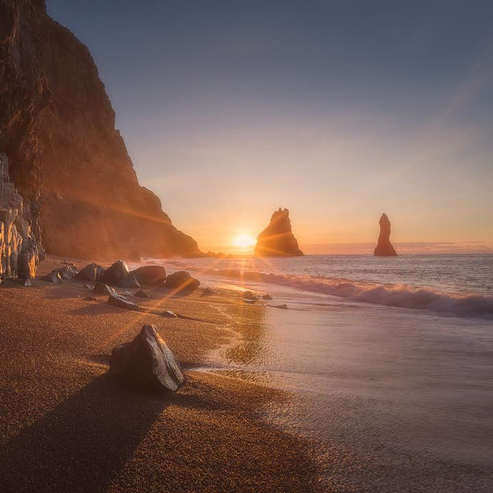 The sun peaking over the horizon over Reynifjara Black Sand Beach. Hexagonal basalt rock columns can be seen in the foreground to the left.