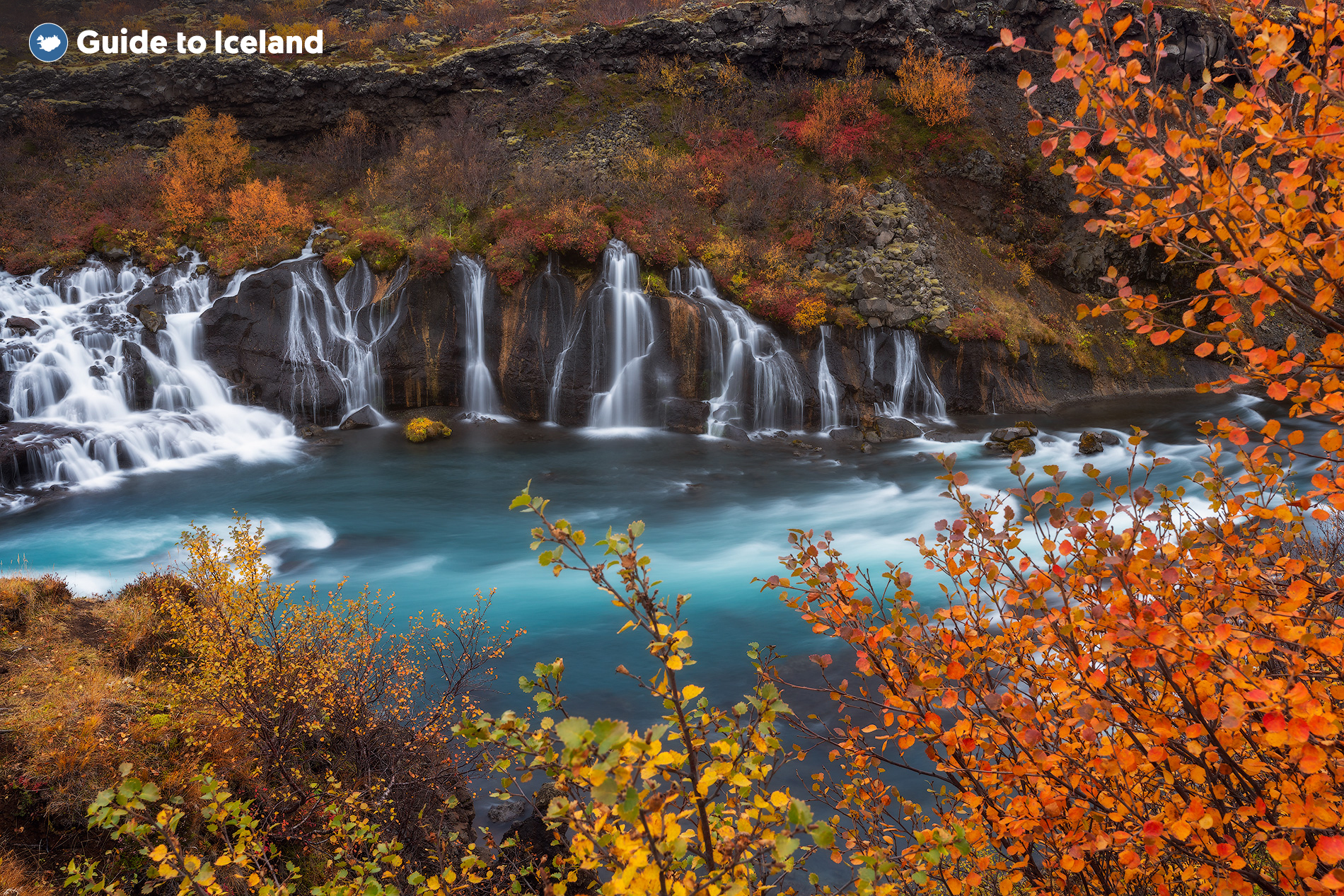 The gentle waterfalls of Hraunfossar trickle from a lava field surrounded by birch forests.