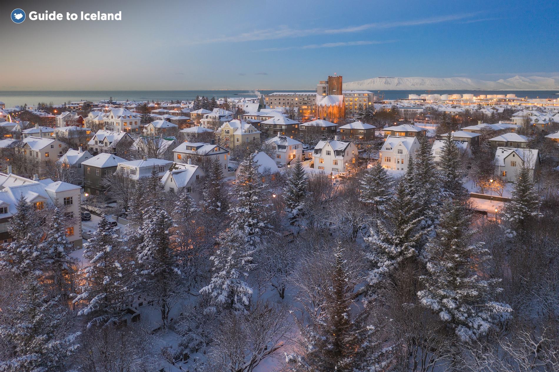 Attraverso il lago ghiacciato di Tjörnin, i visitatori possono ammirare il profilo innevato della città di Reykjavík.