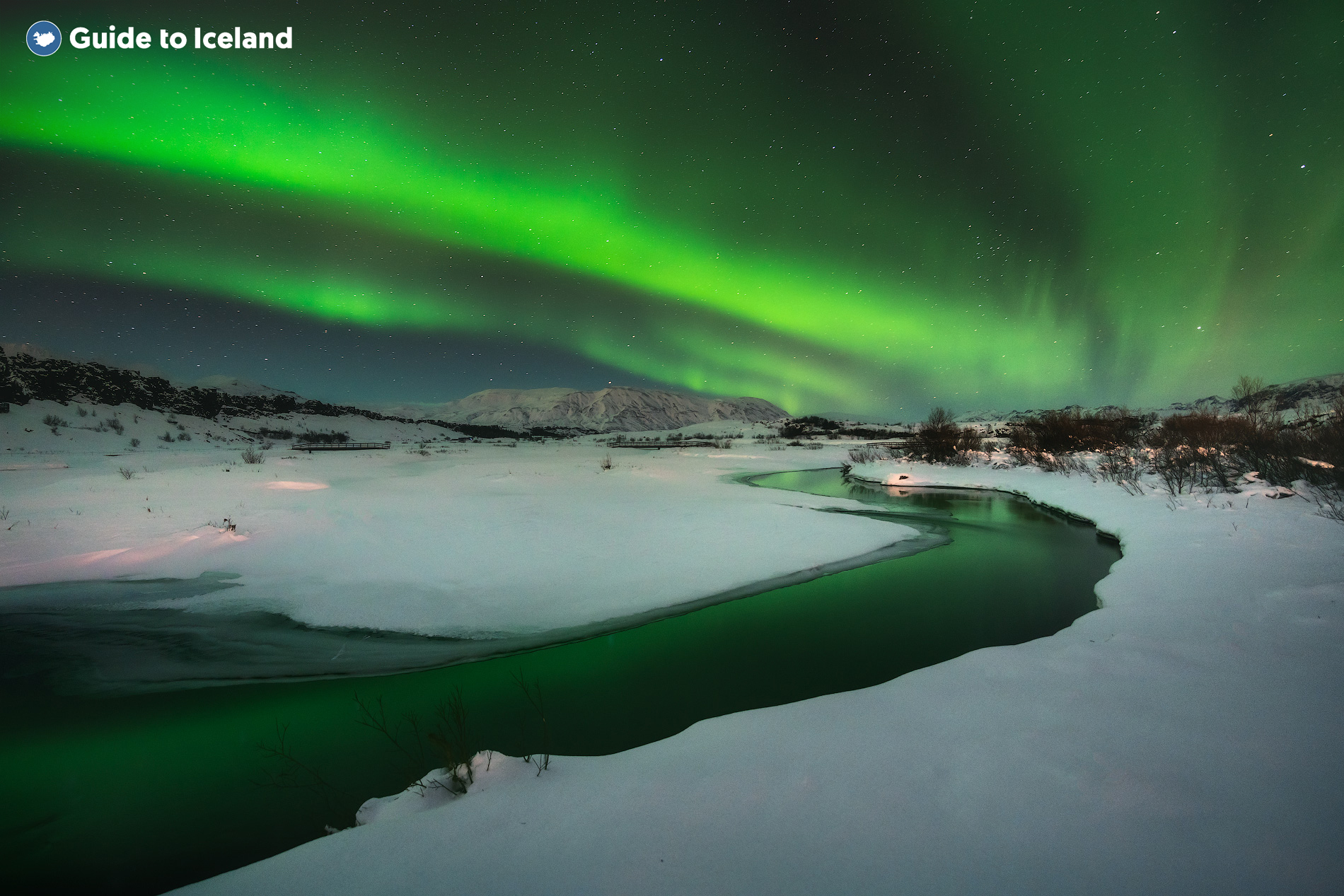A magical dance of the aurora borealis occurs over a snowy landscape in Iceland.