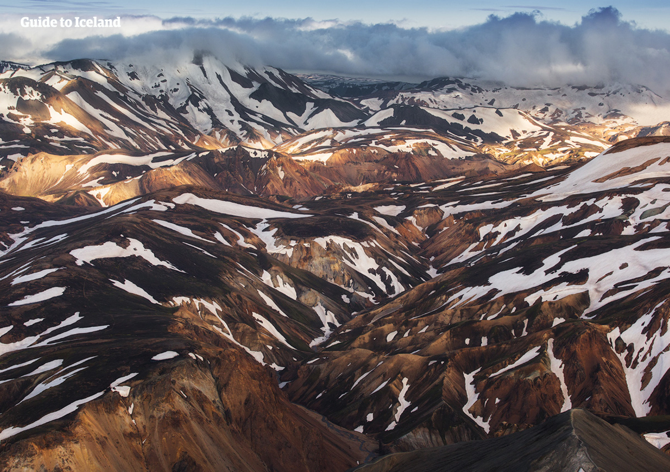 An aerial view of snow-coated mountains in the highlands of Iceland.