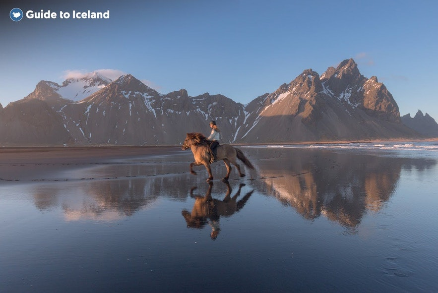 A horseback rider gallops in the shadow of Mount Vestrahorn in East Iceland.