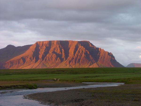 The sun glows on the mountains surrounding Snorrastaðir.