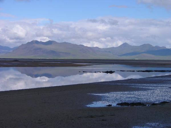 Water flows by the mountains near Snorrastaðir.