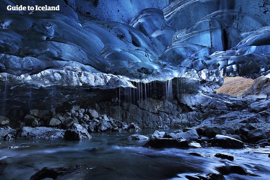 A river streams through an ice cave in Iceland.