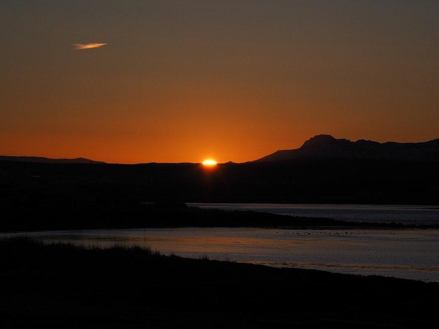 The sun rises at Álftanes Beach.