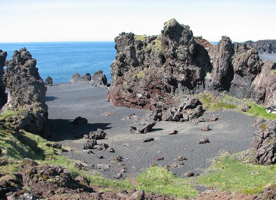 Grass-covered lava formations surround Djúpalónssandur black sand beach.