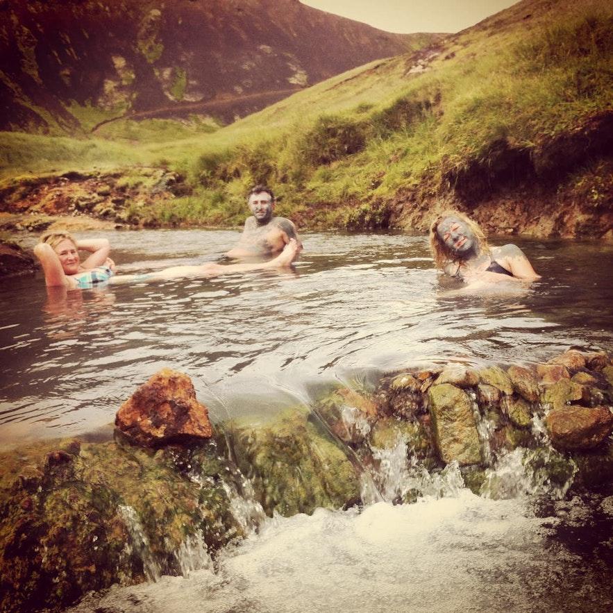 Travelers enjoying a hot spring river in Reykjadalur