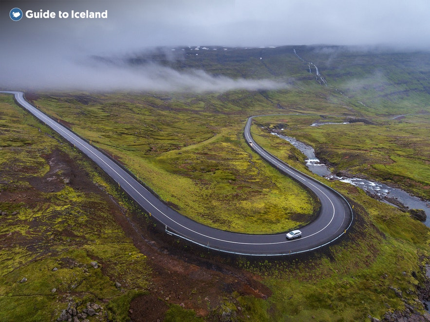 A road winds through the mist towards the Icelandic village of Seydisfjordur.