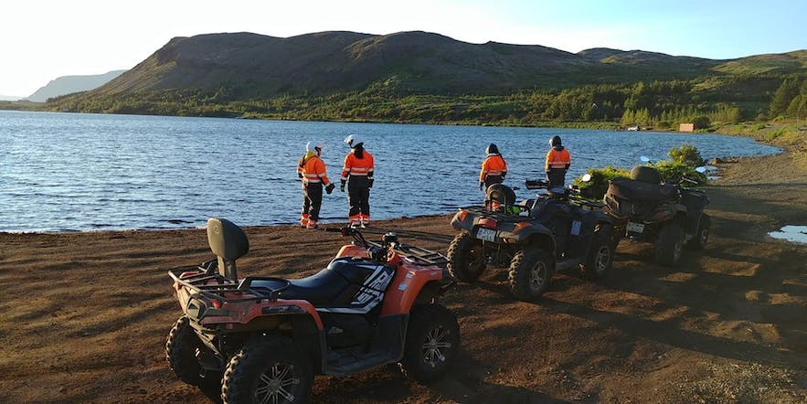 Quadbikers break for photos by a lake in Iceland.