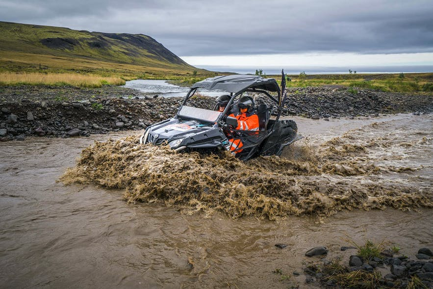 A buggy plunges into a muddy river.