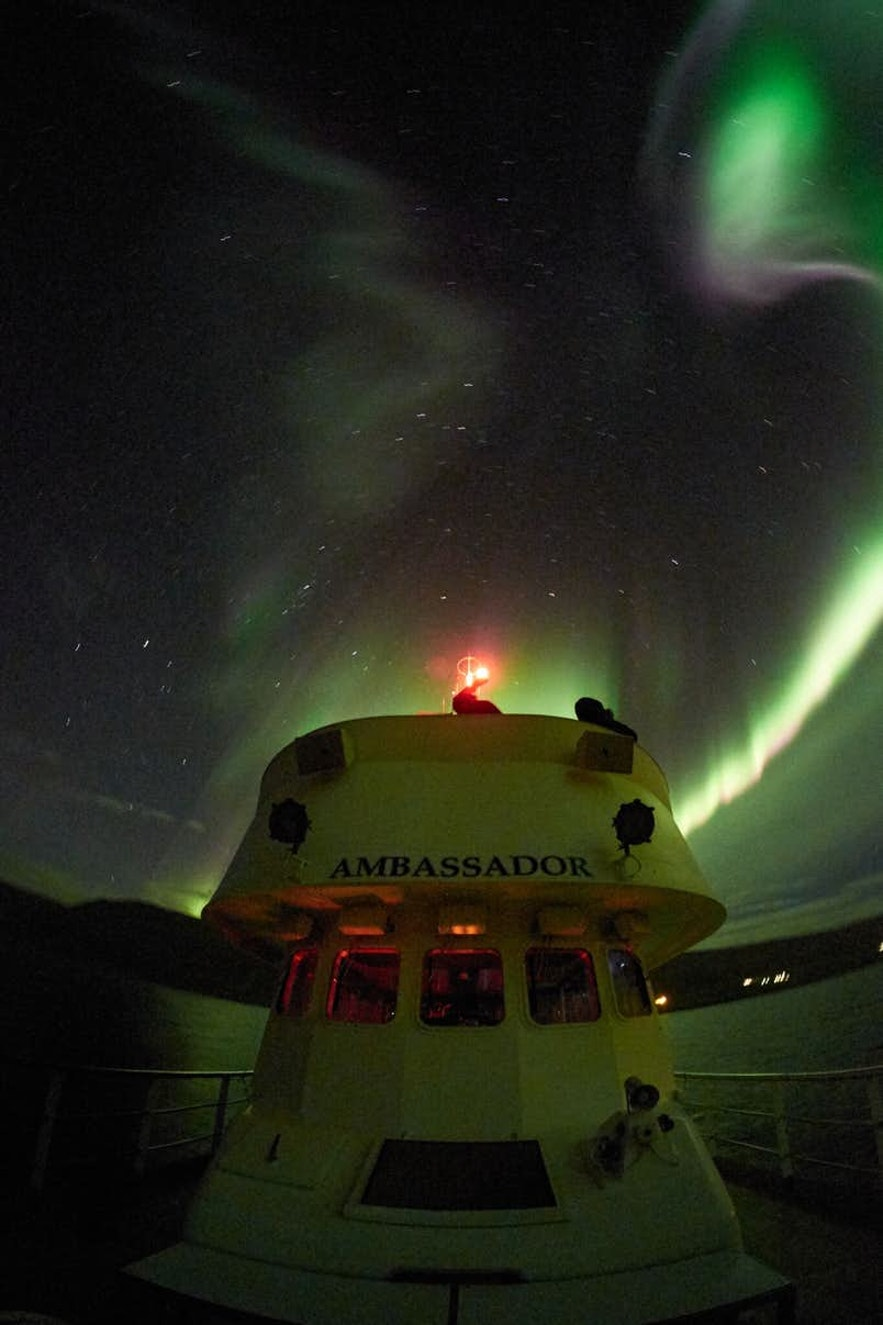 The northern lights dance over a ship in Iceland.