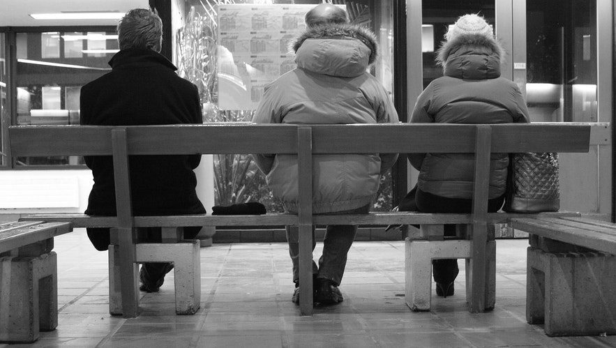 Three people wait for a bus at Hlemmur.