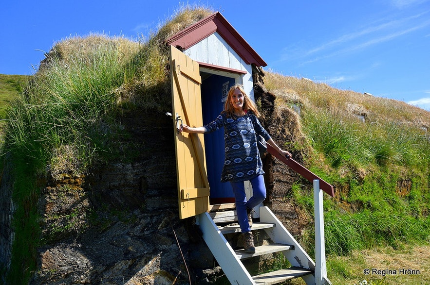 Regína posing by Laufas turf house in Iceland