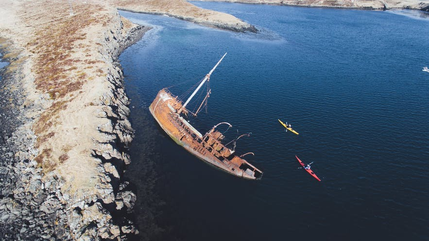 Kayakers pass a shipwreck in Iceland.