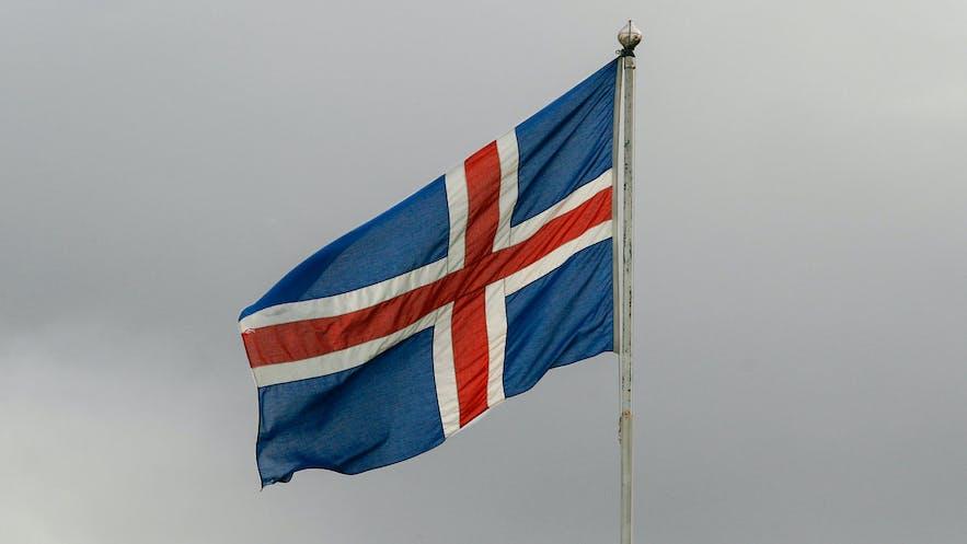 Iceland's flag flies against stormy skies.