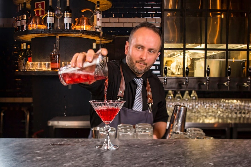 A cocktail maker serves a drink in Iceland.