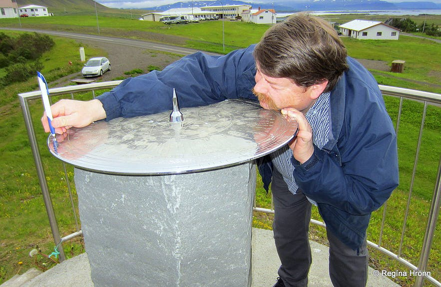 My husband showing me how to use a view dial at The view dial at Hellishólar Westfjords