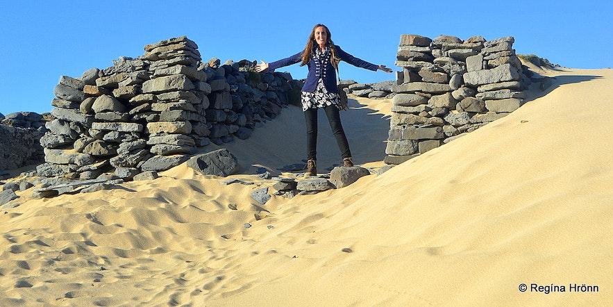 Regína by some of the ruins on the beach in Kollvík