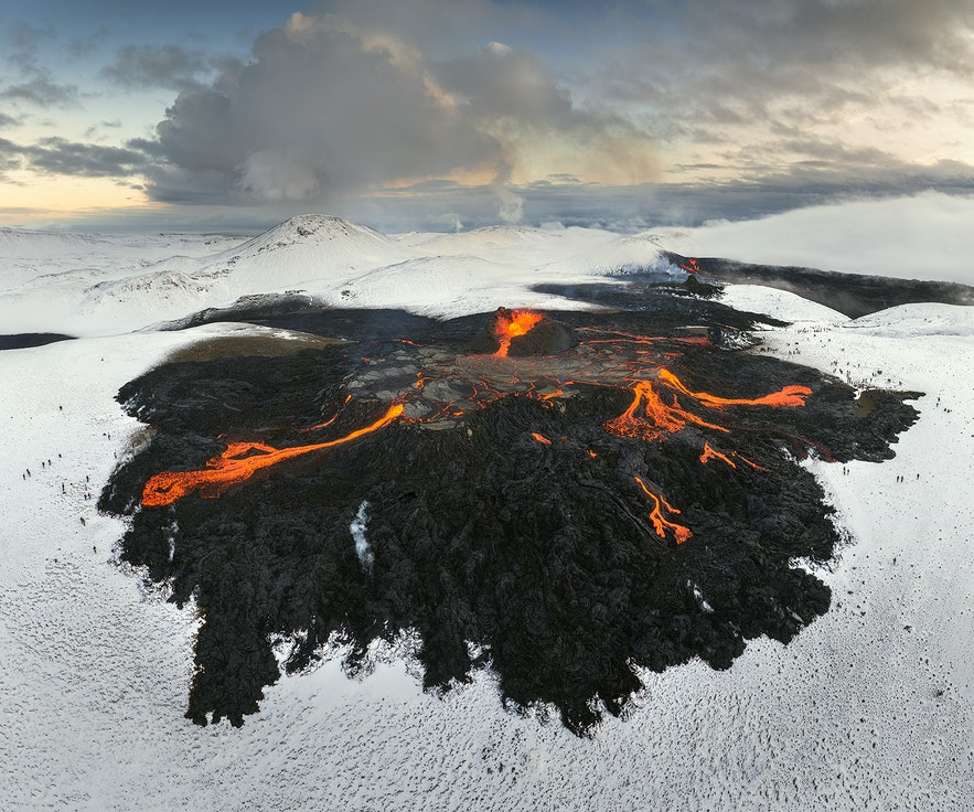 Smoke fills the area above the glowing lava field of the active Geldingadalur volcanic area.