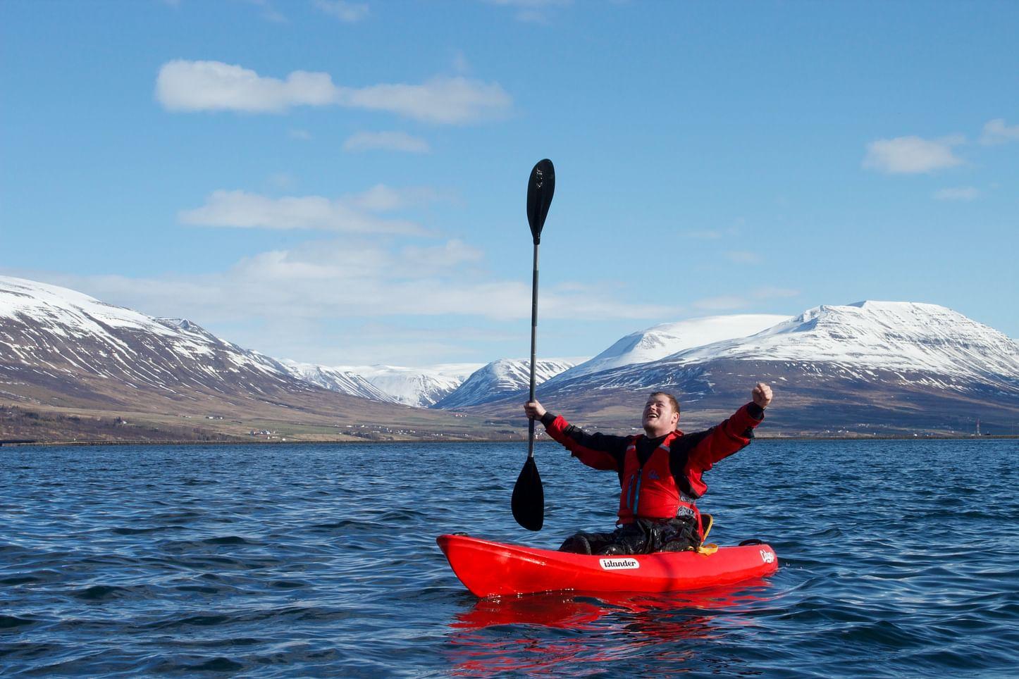 A kayaker cheers in the fjord of Eyjafjordur.