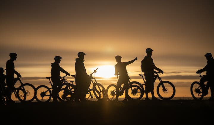 Cyclists travel through the landscapes of North Iceland at sunset.