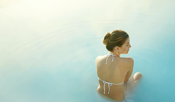 A woman sits in the waters of the Blue Lagoon.