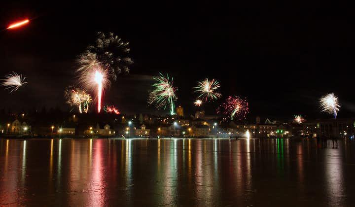 Fireworks bursting over Reykjavik from sea.